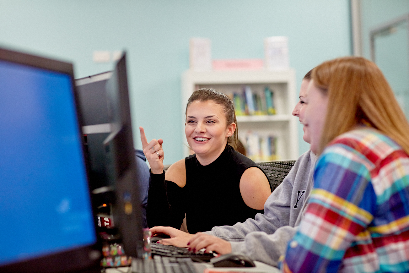 Students laughing while working on open-access PCs together