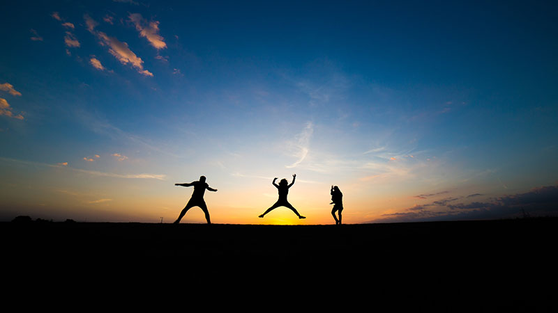 People jumping with sunset in the background